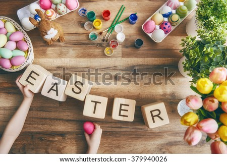 Happy easter! Child painting Easter eggs. Preparing for Easter. On the table lay the cubes with the words Easter. The view from the top. - stock photo