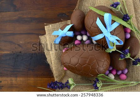 Happy Easter chocolate Easter eggs on dark wood country style table background.  - stock photo