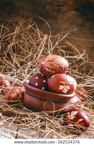 Happy easter! Easter composition with eggs, painted in onion skins with a pattern of natural leaves, rustic style old wooden background and hay, selective focus - stock photo