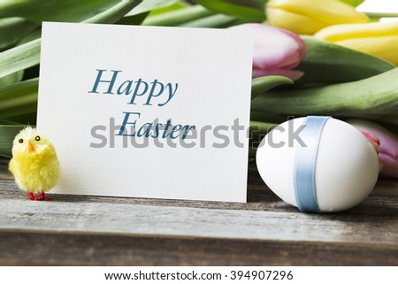 Happy Easter greeting card surrounded by Easter egg, flowers and watchful chick. - stock photo