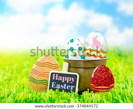 Happy Easter on black clip board with colorful easter eggs on green grass and blue sky,Holiday concept