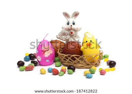 Happy Easter. Rabbit with Easter eggs and colored candies. Photo.