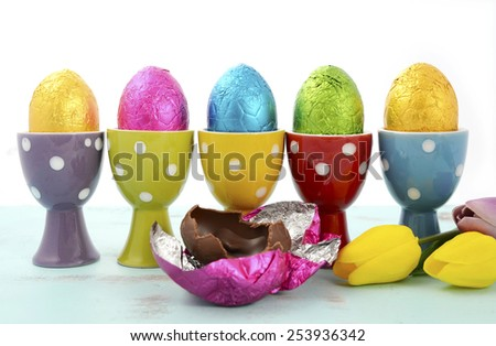 Happy Easter row of chocolate eggs wrapped in bright color foil in red, yellow, blue, green and purple polka dot egg cups. - stock photo