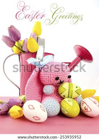 Happy Easter Spring theme pink watering can with easter eggs and handmade crochet knit wool bunny and eggs on pink wood table against a white background, vertical with sample text. - stock photo