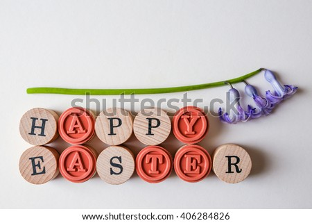 Happy Easter text with fresh spring flower over white background - stock photo