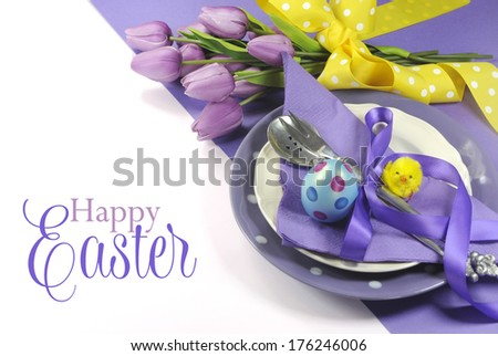 Happy Easter yellow and purple mauve lilac theme easter table place setting, with sample greeting or copy space for your text here. - stock photo
