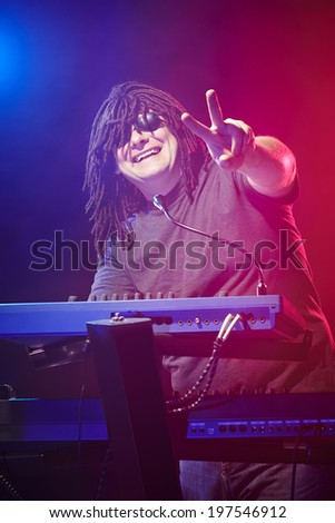Happy ecstatic musician with dreadlocks playing on a keyboard at a concert             - stock photo