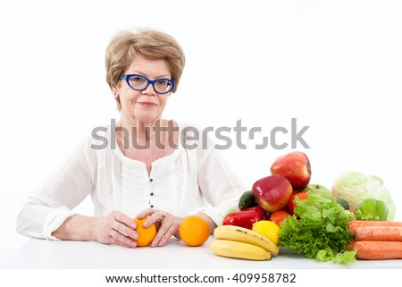 Happy elder Caucasian woman holding hands two oranges, vegetables and fruits are on table, white background - stock photo