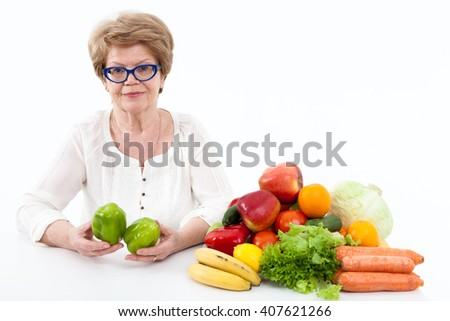 Happy elder Caucasian woman holding hands with two green sweet peppers, vegetables and fruits are on table, white background - stock photo