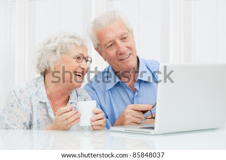 Happy elder couple enjoy together at laptop computer - stock photo