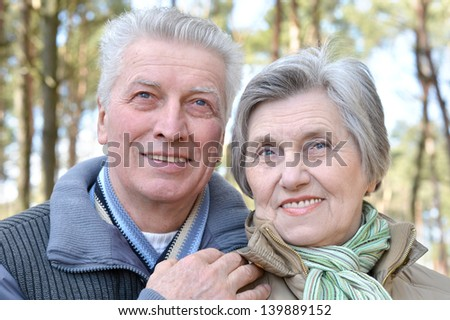 happy elder couple on a walk in the forest in the spring