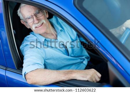 Happy elder man driving a blue car - stock photo