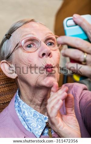 Happy elder woman taking duck face selfie - stock photo