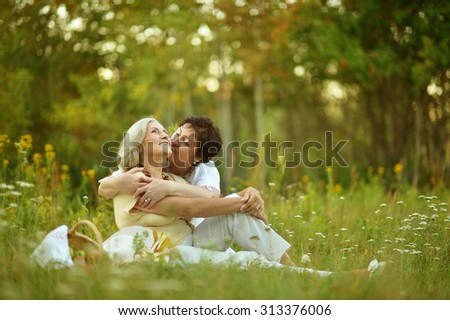 Happy elder women resting on grass at nature