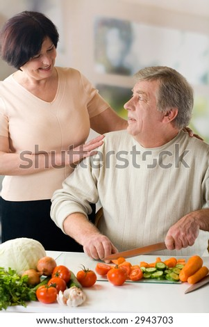 Happy elderly couple cooking at kitchen - stock photo