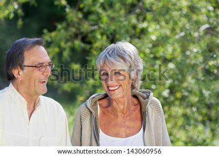 Happy elderly couple enjoying the greenery in a park.