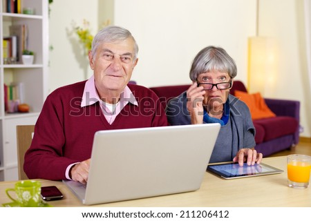Happy elderly couple having fun with technology tablet and pc - stock photo