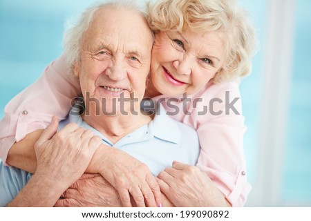 Happy elderly couple hugging in front of the camera - stock photo