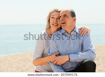 Happy elderly couple hugging outdoor on seaside - stock photo