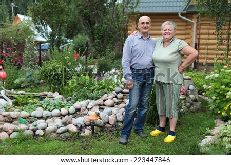 Happy elderly couple in the garden of a country house - stock photo