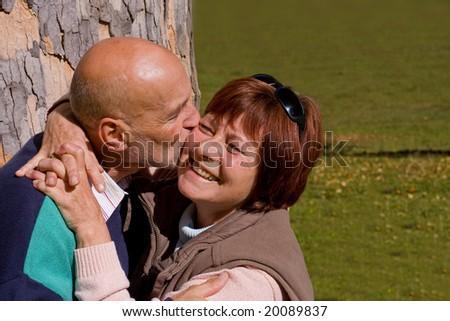 happy elderly couple kissing - stock photo