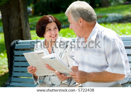 Happy elderly couple reading together outdoors. Focus on woman - stock photo