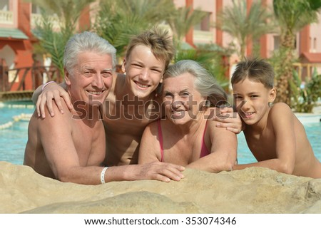 Happy Elderly couple resting at pool together with grandsons - stock photo