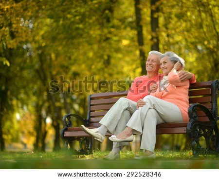 Happy elderly couple sitting on bench in autumn park - stock photo