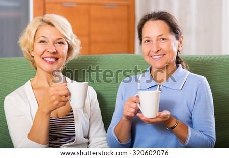 Happy elderly female having tea break at office. Focus on blonde woman - stock photo