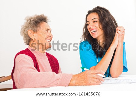 Happy elderly lady laughing with kind nurse carer working in homecare. - stock photo