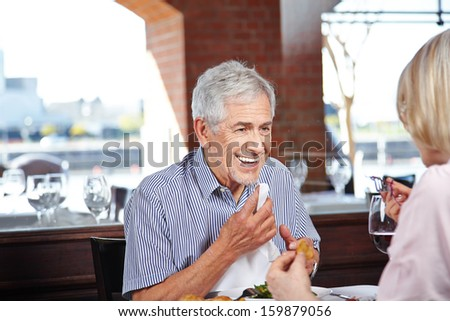 Happy elderly man cleaning his mouth with napkin at a restaurant - stock photo