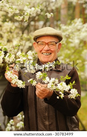 Happy elderly man in the garden - stock photo