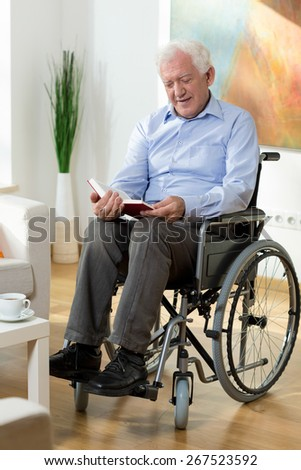 Happy elderly man reading book at home - stock photo