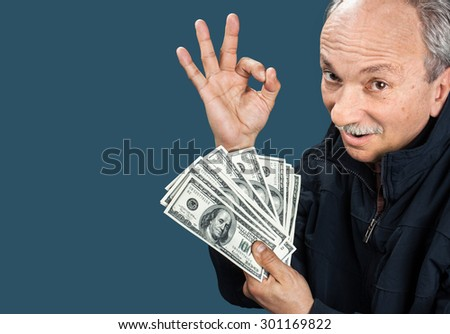 Happy elderly man showing fan of money and sign OK with fingers on blue background with copy-space