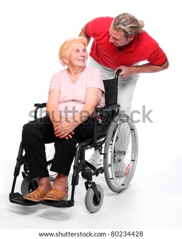 Happy elderly paraplegic woman sitting in a wheelchair and her male nurse. - stock photo