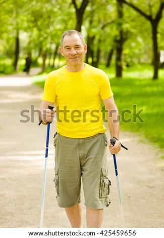 Happy elderly people engaged in Nordic walking - stock photo