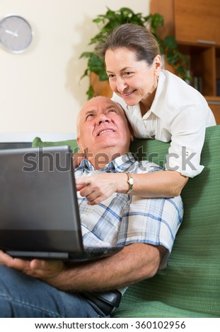 Happy elderly russian  man and mature woman using laptop at home
