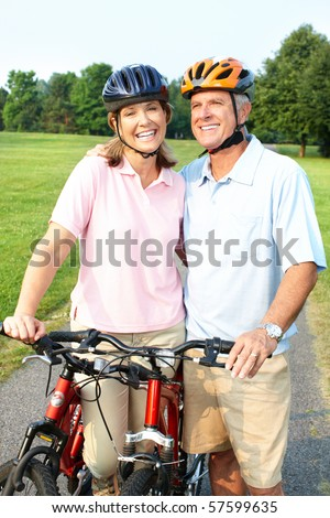 Happy elderly senior couple cycling in park - stock photo