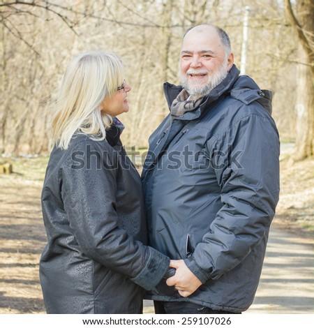 Happy Elderly Senior Romantic Couple holding hands in nature, Old people portrait outdoor winter autumn season. - stock photo
