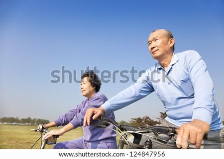 Happy elderly seniors couple biking - stock photo