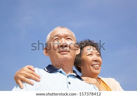 Happy elderly seniors couple with cloud background - stock photo