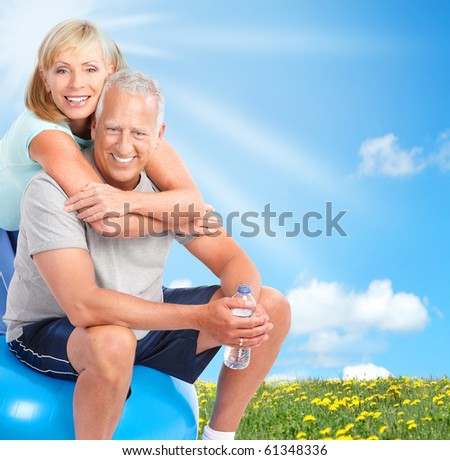 Happy elderly seniors couple working out in park - stock photo