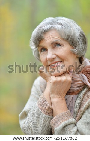 Happy elderly woman enjoying in autumn park