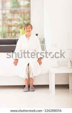 happy elderly woman in pajamas sitting on bed - stock photo