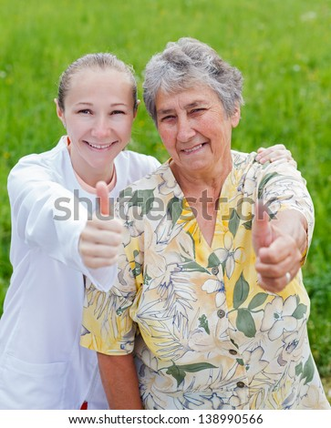 Happy elderly woman satisfied with her caretaker - stock photo