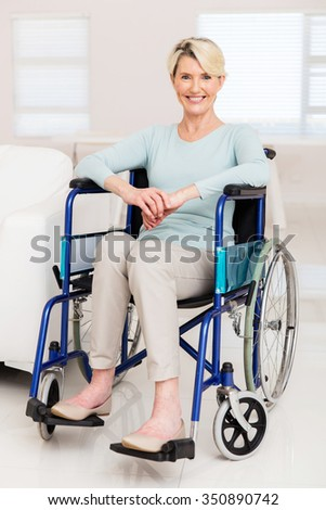 happy elderly woman sitting on wheelchair at home - stock photo