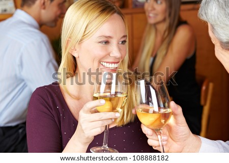 Happy elderly woman toasting with glass of white wine to man - stock photo