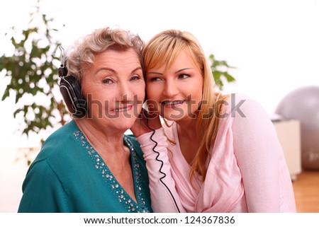 Happy elderly woman with granddaughter listening to the music at home