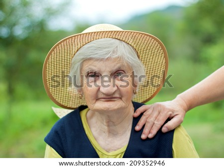 Happy elderly woman with hat in the garden - stock photo