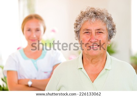 Happy elderly woman with her caregiver in the background - stock photo
